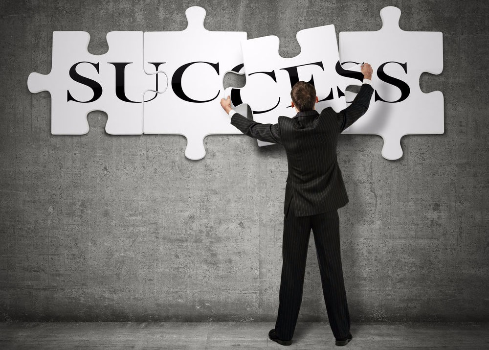 Image of a man standing in front of a jigsaw puzzle with the words success.